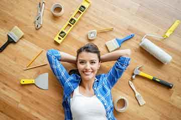 woman lying on floor next to home improvement tools